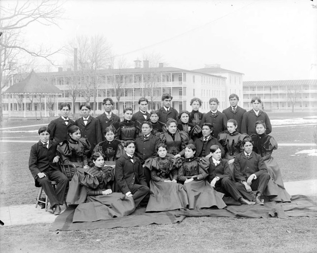 Group_of_Male_and_Female_Students;_Brick_Dormitories_And_Bandstand_in_Background_1879